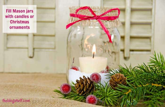 Mason jar decorated with candle, berries and greenery